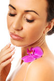 Woman with purple orchid petal on shoulder Stock Photography