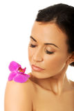 Woman with purple orchid petal on shoulder Stock Photo