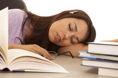 Woman purple shirt asleep pen in ear books Royalty Free Stock Image