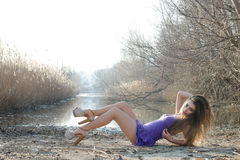 Woman in a purple short dress lying on dry reeds Royalty Free Stock Images