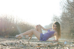 Woman in a purple short dress lying on dry reeds Royalty Free Stock Photos
