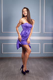 Woman in purple silk waving dress Stock Images