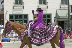 Woman with purple Spanish dress riding horse during opening day parade down State Street, Santa Barbara, CA, Old Spanish Days Fies Royalty Free Stock Photos