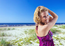 Woman in purple sundress on a beach. Royalty Free Stock Photography