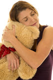 Woman in purple tank hug bear closed eyes Royalty Free Stock Photos