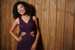 Woman in Purple V-neck Cutout Dress Leaning on Brown Wooden Wall Stock Photos