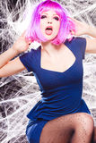 Woman with purple wig and intense make-up trapped in a spider web Stock Images