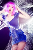 Woman with purple wig and intense make-up trapped in a spider web screaming Royalty Free Stock Photos