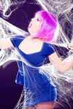 Woman with purple wig and intense make-up trapped in a spider web screaming Stock Photography