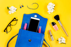 Woman purse, beauty products, smartphone, glasses on a bright yellow background, top view. Things from a woman purse, female accessories on a bright colorful Stock Photo