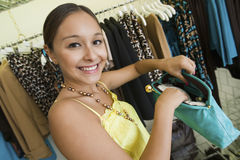 Woman With Purse In Boutique. Portrait of a smiling young woman with purse in the boutique Royalty Free Stock Photos