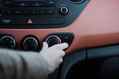 Woman push the button in car Stock Photography