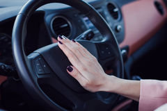 Woman push the button on a steering wheel in car Royalty Free Stock Photo