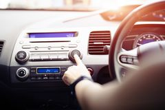 Woman push turn on music radio in passenger car stock photography