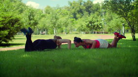 Woman push up exercise. Fitness woman pushing on green grass at park. Two women doing pushups exercise outdoor. Push ups with knees. Outdoor fitness training stock video footage