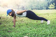 Woman push-up exercise workout fitness doing outside on grass i royalty free stock photos