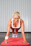 Woman push ups. Young fitness woman doing push ups stock image