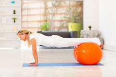 Woman push ups. Middle aged woman doing push ups with exercise ball stock images