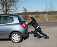 Woman pushes her car Royalty Free Stock Images