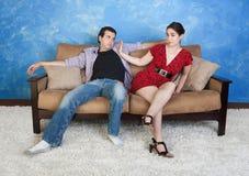 Woman Pushes Man Away. Beautiful women pushes sloppy men away on sofa Stock Photo