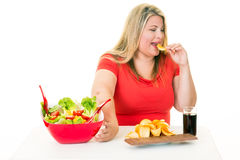 Woman pushing away salad and eating junk food Royalty Free Stock Image