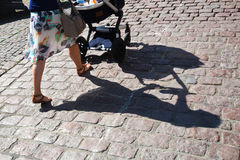 Woman pushing a baby buggy in the city Royalty Free Stock Photography