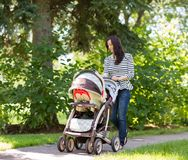 Woman Pushing Baby Carriage In Park. Happy young woman pushing baby carriage in park stock image