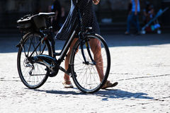 Woman pushing a bike in the city Royalty Free Stock Photo