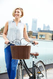 Woman Pushing Bike With City Skyline In Background Royalty Free Stock Images
