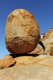Woman Pushing Boulder. In a sisyphean task a woman in high heel shoes tries to push a huge boulder Stock Image