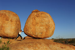 Woman Pushing Boulder. In a sisyphean task a woman in high heel shoes tries to push a huge boulder Royalty Free Stock Images