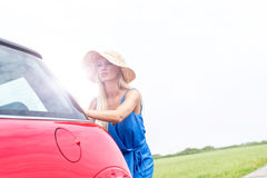 Woman pushing broken down car against clear sky Stock Photography