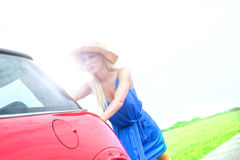 Woman pushing broken down car on country road against clear sky Stock Photos