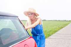 Woman pushing broken down car on country road against clear sky Stock Photography