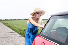 Woman pushing broken down car on country road against clear sky Royalty Free Stock Photography