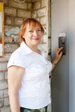 Woman pushing button of house intercom Royalty Free Stock Photo