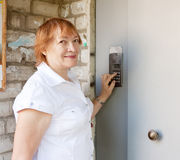 Woman pushing button of house intercom Stock Image