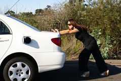 Woman Pushing Car Out of Gas royalty free stock image
