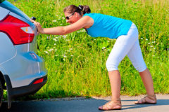 Woman pushing car out of gasoline Royalty Free Stock Photography