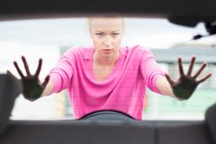 Woman pushing a car. Stock Photos