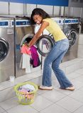 Woman Pushing Clothes In Washing Machine. Portrait of young African American woman pushing clothes in washing machine at laundry royalty free stock photography