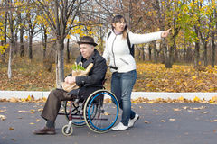 Woman pushing an elderly man in a wheelchair. Woman pushing an elderly men in a wheelchair stretching out her arm pointing to something and calling out as they Stock Image