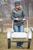 Woman pushing empty barrow Stock Images