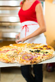 Woman pushing the finished pizza from the oven Stock Photos