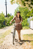 Woman pushing her bike on a country track Royalty Free Stock Photography