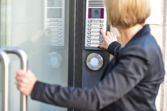 Woman pushing a intercom button. Middle aged woman pushing button of intercom Stock Photography