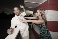 Woman pushing the man over the edge Stock Photography