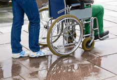 Woman pushing man in wheelchair Royalty Free Stock Images