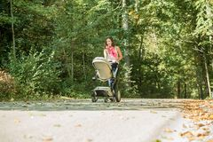 Woman pushing a pram or baby carriage Royalty Free Stock Photography