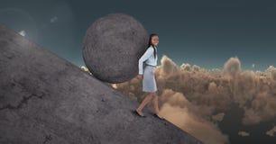 Woman pushing rolling round rock Stock Photos